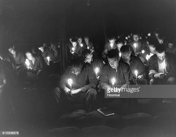 CB's of 50th Battalion sitting on sandbags in a Canvas NCB Chapel bow their heads in prayer during candle light Holy Communion sevice at Tinian...