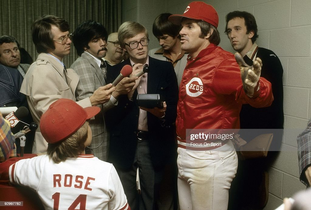 Outfielder Pete Rose (R) of the Cincinnati Reds talks with the media as Pete Rose Jr. #14 looks on after a MLB baseball game circa early 1970's at Riverfront Stadium in Cincinnati, Ohio. Rose Played for the Reds from 1963-78.