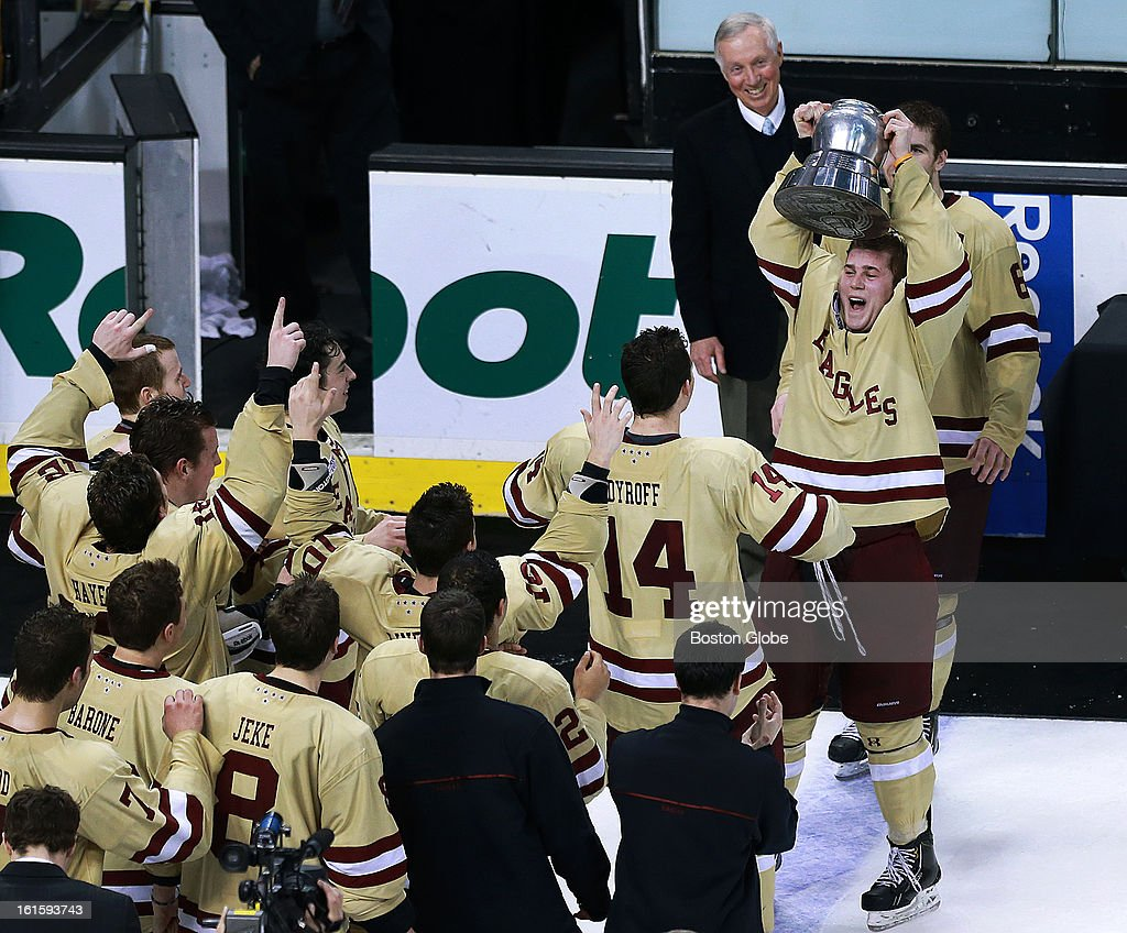 BC's Pat Mullane raises the Beanpot first, as head coach Jerry York smiles in the background, and his teammates wait for their turn in the foreground. Boston College and Northeastern University met in the championship game of the Beanpot Tournament at the TD Garden.