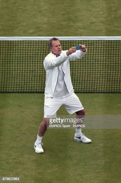 USA's Patrick McEnroe takes a photograph during his match with partner Patrick McEnroe against Australia's Paul McNamee and Peter McNamara in their...