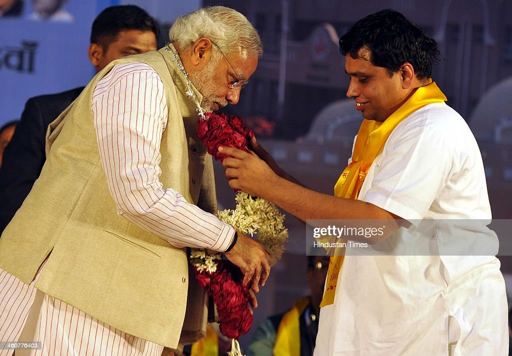 BJP's PM candidate and Gujarat Chief Minister Narendra Modi with Yog Guru Bal Krishan at the 5th foundation day celebrations of 'Bharat Swabhiman' on January 5, 2014 in New Delhi, India. Launching a fresh offensive against the Congress, Modi said, ''Dont trust anyone because of mere promises. Judge the track-record, and not tape record.' Modi promised to review and reform of the taxation system in the country, saying the existing structure is a burden on common man. Modi pointed out Ramdev, who had said his support to the saffron party would be issue-based, had joined the peoples movement. Modi further said, We have the will-power to transform the country. The way to end corruption is by making the state progressive and policy driven.'