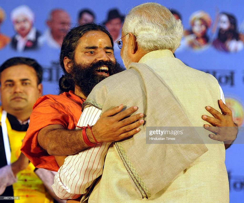 BJP's PM candidate and Gujarat Chief Minister Narendra Modi with Yog Guru Baba Ramdev at the 5th foundation day celebrations of 'Bharat Swabhiman' on January 5, 2014 in New Delhi, India. Launching a fresh offensive against the Congress, Modi said, ''Dont trust anyone because of mere promises. Judge the track-record, and not tape record.' Modi promised to review and reform of the taxation system in the country, saying the existing structure is a burden on common man. Modi pointed out Ramdev, who had said his support to the saffron party would be issue-based, had joined the peoples movement. Modi further said, We have the will-power to transform the country. The way to end corruption is by making the state progressive and policy driven.'