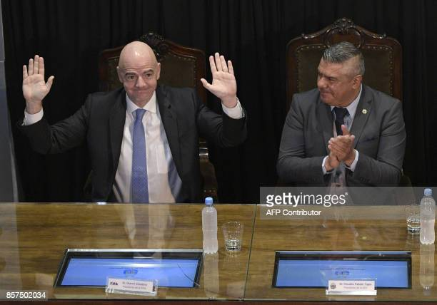 FIFA's President Gianni Infantino waves next to AFA's President Claudio Tapia at Argentine Football Assosiation headquarters in Buenos Aires on...