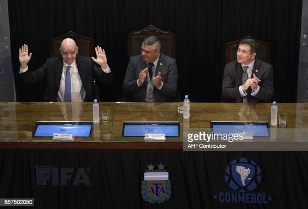 FIFA's President Gianni Infantino waves next to AFA's President Claudio Tapia and CONMEBOL's President Alejandro Dominguez at Argentine Football...