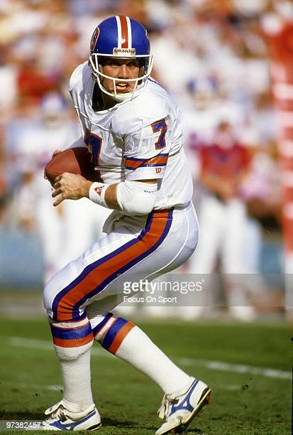 CIRCA 1980's Quarterback John Elway of the Denver Broncos scrambles with the ball circa 1980's during an NFL football game Elway played for the...