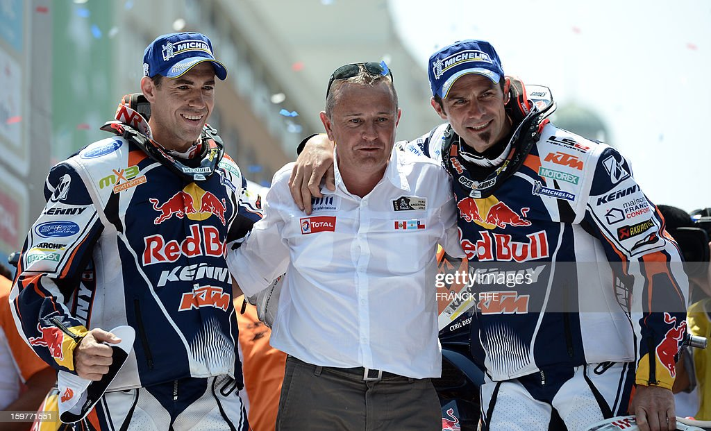 KTM's rider Cyril Despres (R) of France and KTM's rider Ruben Faria of Portugal (L) pose with Dakar Rally director Etienne Lavigne on the podium of the Dakar 2013 in Santiago, Chile on January 20, 2013. Stephane Peterhansel claimed a record fifth Dakar Rally drivers title, and 11th overall of his career, while French compatriot Cyril Despres captured a fifth motorcycling crown.