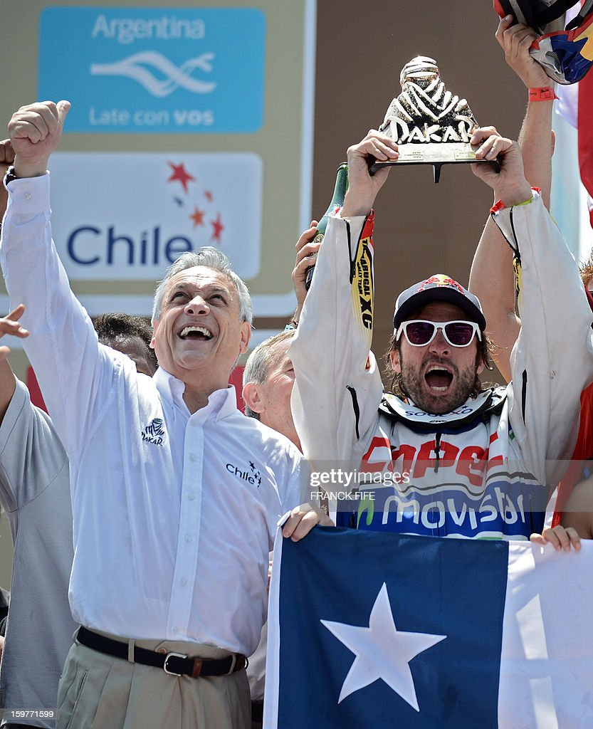 KTM's rider Francisco Chaleco Lopez (R) of Chile celebrates with his trophy next to Chilean President Sebastian Pinera on the podium of the Dakar 2013 in Santiago, Chile on January 20, 2013. KTM's rider French Cyril Despres won the Dakar 2013 ahead of KTM's rider Ruben Faria of Portugal KTM's rider Francisco Chaleco Lopez of Chile.