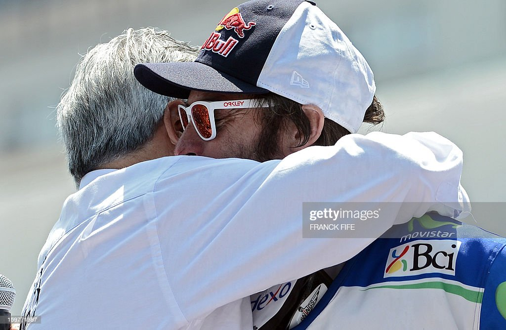 KTM's rider Francisco Chaleco Lopez (R) of Chile is embraced by Chilean President Sebastian Pinera on the podium of the Dakar 2013 in Santiago, Chile on January 20, 2013. KTM's rider French Cyril Despres won the Dakar 2013 ahead of KTM's rider Ruben Faria of Portugal KTM's rider Francisco Chaleco Lopez of Chile.