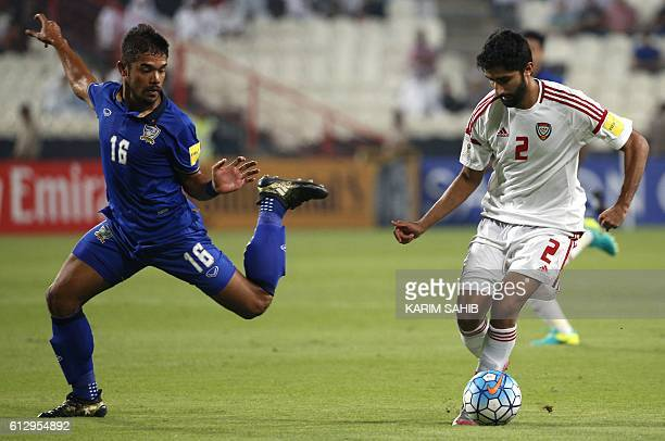 UAE's Salem Saleh dribbles by Thailand's Pratum Chuthong during the 2018 FIFA World Cup Qualifiers match between United Arab Emirates and Thailand at...