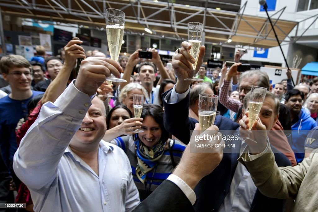 CERN's scientists celebrates with champagne after the annoucement of the winners of the Nobel Prize for Physics on October 8, 2013 in Meyrin near Geneva. Peter Higgs of Britain and Francois Englert of Belgium won the Nobel Prize for Physics for conceiving of the so-called 'God particle' which confers mass. The presumed particle was discovered last year by Europe's mega-scale physics lab at CERN, near Geneva, after a decades-long search. COFFRINI