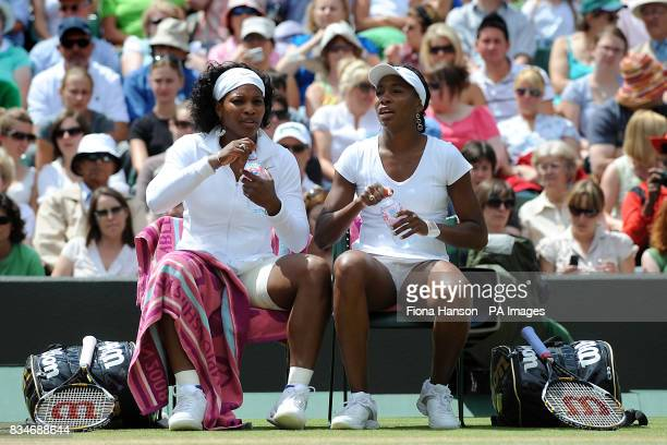 USA's Serena and Venus Williams take a drinks break during their doubles match in the Wimbledon Championships 2008 at the All England Tennis Club in...