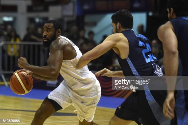 USA's small forward Reginald Williams II drives the ball marked by Argentina's small forward Patricio Garino during their 2017 FIBA Americas...