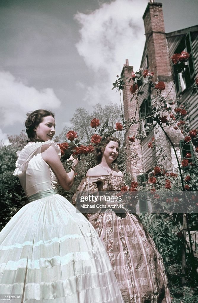 MID 1930's Southern Belles stop and smell the roses during a recreation of pre Civil War life on a plantation circa mid 1930's in the deep south