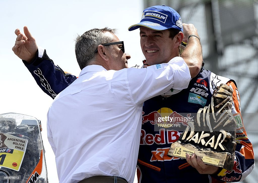 KTM's Spanish biker <a gi-track='captionPersonalityLinkClicked' href=/galleries/search?phrase=Marc+Coma&family=editorial&specificpeople=767761 ng-click='$event.stopPropagation()'>Marc Coma</a> (R) receives his trophy from Dakar director <a gi-track='captionPersonalityLinkClicked' href=/galleries/search?phrase=Etienne+Lavigne&family=editorial&specificpeople=643127 ng-click='$event.stopPropagation()'>Etienne Lavigne</a> on the podium in Buenos Aires, Argentina, on January 17, 2015. Coma won the Dakar Rally motorcycle title for the fifth time, ahead Portuguese Paulo Goncalvez and Australian Toby Price. AFP PHOTO / FRANCK FIFE