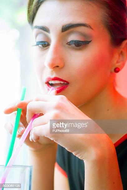 1950's Style - Portrait of beautiful woman using drinking straw