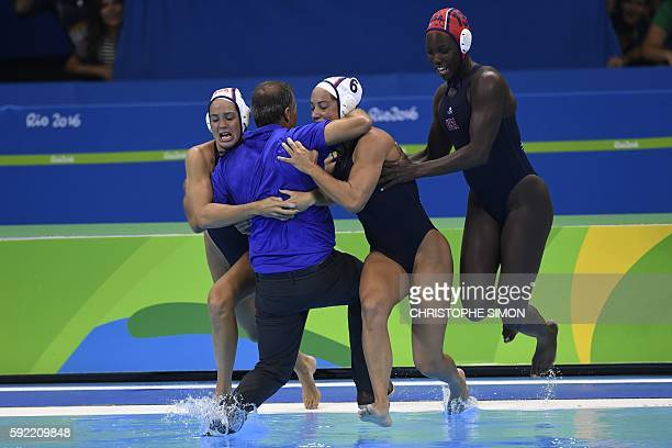 TOPSHOT USA's team jump with their coach Adam Krikorian in the pool after winning the women's water polo final between Italy and USA at the Rio 2016...