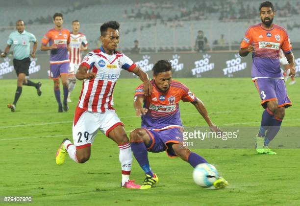 ATK's Th Bipin Singh vies for the ball with FC Pune City's Lalchhunmawia Fanai during the Indian Super League football match between ATK and FC Pune...