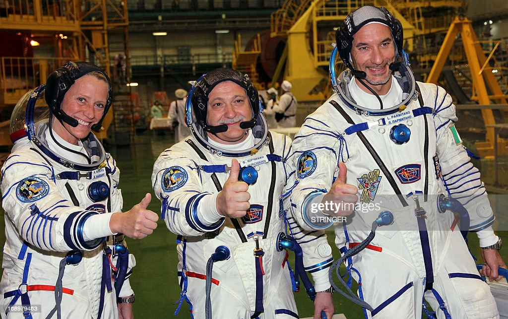 NASA's US astronaut Karen Nyberg (L), Russian cosmonaut Fyodor Yurchikhin (C) and European Space Agency (ESA) Italian astronaut Luca Parmitano (R) give a thumbs-up as they take part in pre-flight training at the Russian-leased Baikonur cosmodrome on May 17, 2013. The crew is scheduled to blast off to the International Space Station (ISS) from Kazakhstan's Baikonur cosmodrome on May 29. AFP PHOTO / STRINGER