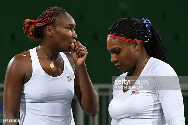 USA's Venus Williams speaks to USA's Serena Williams during their women's first round doubles tennis match against Czech Republic's Lucie Safarova...