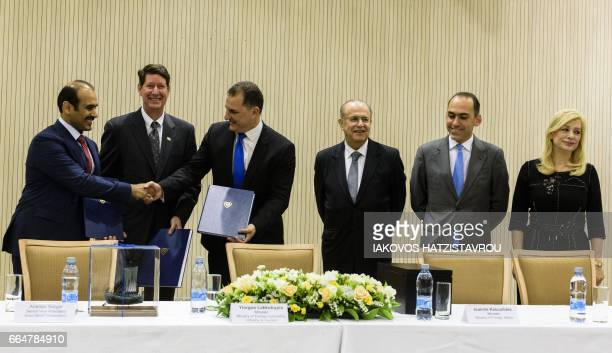 Saad Sherida AlKaabi President and of CEO Qatar Petroleum shakes hands with Cypriot Energy Minister George Lakkotrypis as Andrew Swiger Senior Vice...