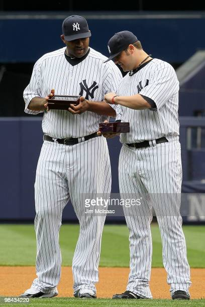 CC Sabathia and Joba Chamberlain of the New York Yankees look at their 2009 World Series rings after they received them prior to playing against the...