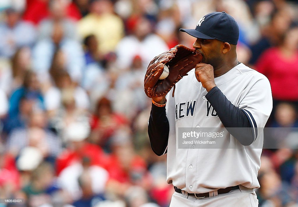 CC Sabathia #52 of the New York Yankees bites his glove in between pitches in the fifth inning against the Boston Red Sox during the game on September 14, 2013 at Fenway Park in Boston, Massachusetts.