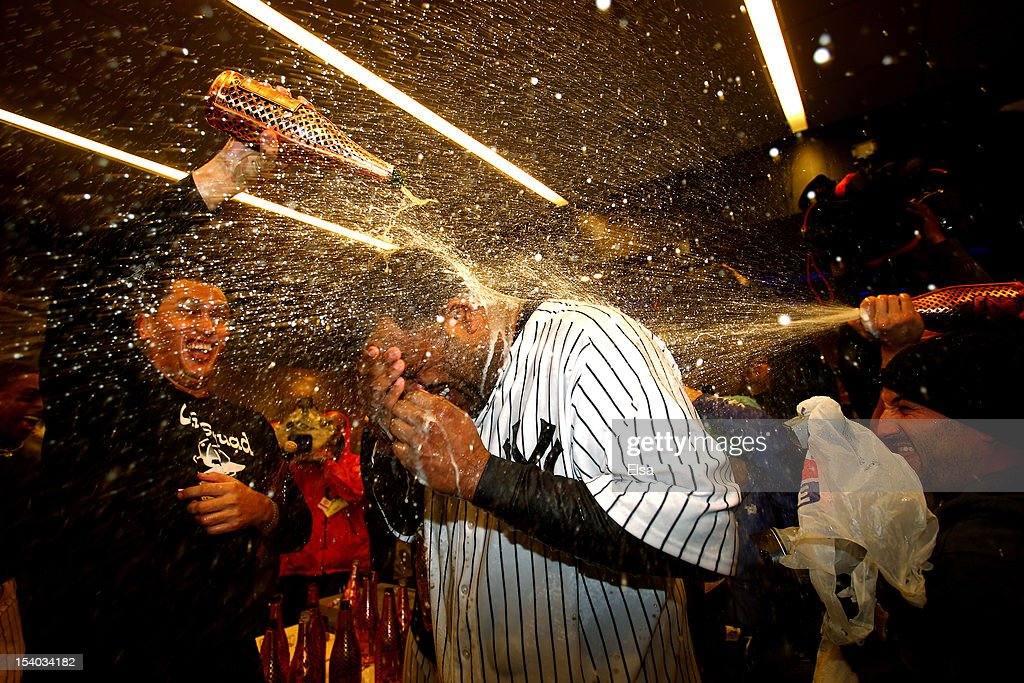 CC Sabathia #52 of the New York Yankees celebrate in the locker room after defeating the Baltimore Orioles by a score of 3-1 to win Game Five of the American League Division Series at Yankee Stadium on October 12, 2012 in New York, New York.