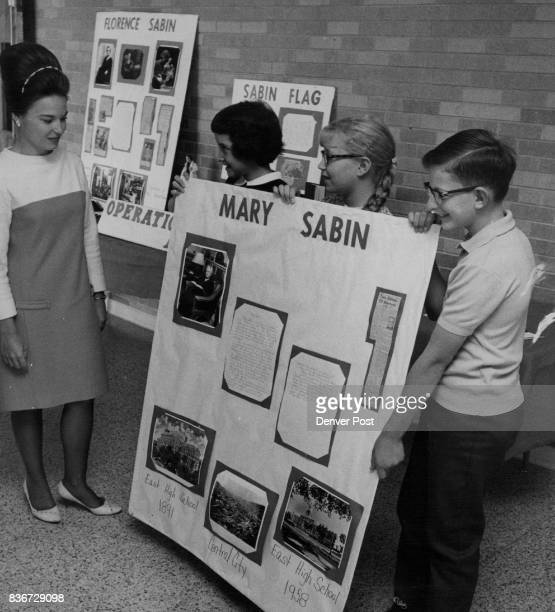 Sabin sixth graders examine poster about school Mrs Nanette Page left one of the teachers who guided the children in a school pride building project...