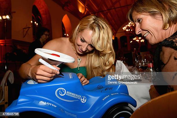 Sabine Lisicki of Germany signs a Bobby Car during Day Three of the Nuernberger Versicherungscup 2015 on May 18 2015 in Nuremberg Germany