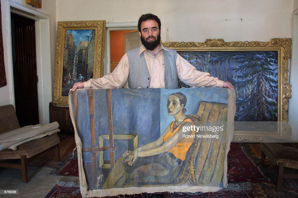 Sabir Latifi, a Kabul businessman, holds up a painting November 25, 2001 he helped to rescue along with 50 others from Kabul's National Gallery during the last days of the Taliban regime. Latifi had heard of the Taliban's intention to destroy the National Gallery's archive of paintings of living figures. He paid a bribe of $5000 USD to a Taliban official and had the 50 canvases delivered to his house late in the evening on a bicycle. At present, Latifi has few details as to who the painters are, their time period or how they were acquired by the National Gallery.