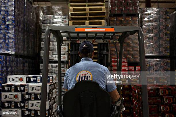 A SABMiller Miller Lite logo appears on the shirt of a worker as beer is gathered for a customer order at the Baumgarten Distributing Co warehouse in...