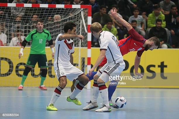 Saboor Khalili and Adam Fiedler of Germany and Richard Ward of England compete for the ball during the Futsal International Friendly match between...