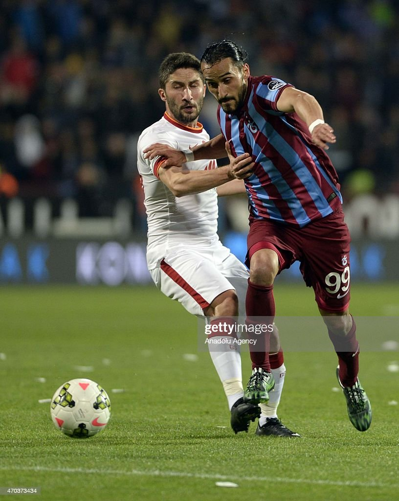 Sabri Sarioglu (L) of Galatasaray in action against Erkan Zengin (99) of Trabzonspor during the Turkish Spor Toto Super League soccer match between Trabzonspor and Galatasaray at Avni Aker Stadium in Turkey on April 19, 2015.