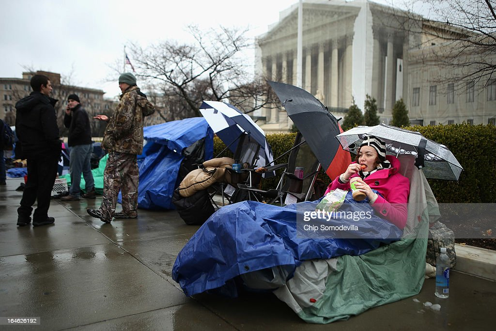 Sabrina Canela, 20, takes shelter from the rain underneath a tarp and umbrella while waiting in line in front of the U.S. Supreme Court March 25, 2013 in Washington, DC. Canela is 38th in line for a chance to attend the court's hour-long argument on Tuesday morning over the constitutionality of Proposition 8, California's ban on same-sex marriage.