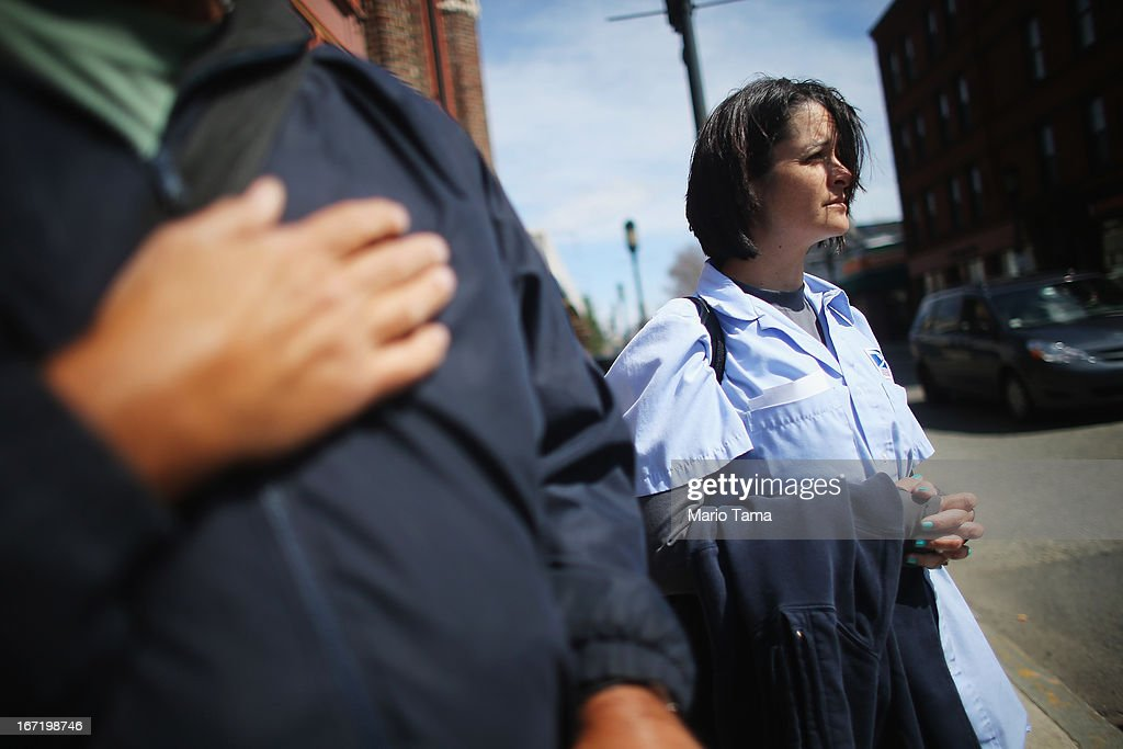 Sabrina Fucile watches next to a man holding his hand to his heart during the funeral procession for 29-year-old Krystle Campbell, who was one of three people killed in the Boston Marathon bombings, on April 22, 2013 in Medford, Massachusetts. The 29-year-old restaurant manager was raised in Medford. Massachusetts Gov. Deval Patrick has asked residents to observe a moment of silence at the time of the first explosion at 2:50 p.m. this afternoon.