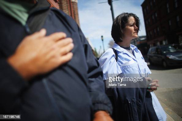 Sabrina Fucile watches next to a man holding his hand to his heart during the funeral procession for 29yearold Krystle Campbell who was one of three...