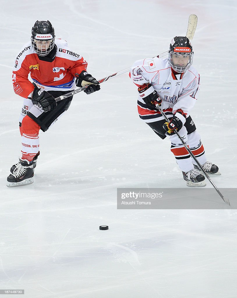 Sabrina Zollinger (L) of Switzerland and Yurie Adachi (R) of Japan in action in the match between Japan and Switzerland during day three of the Ice Hockey Women's 5 Nations Tournament at the Shin Yokohama Skate Center on November 9, 2013 in Yokohama, Japan.