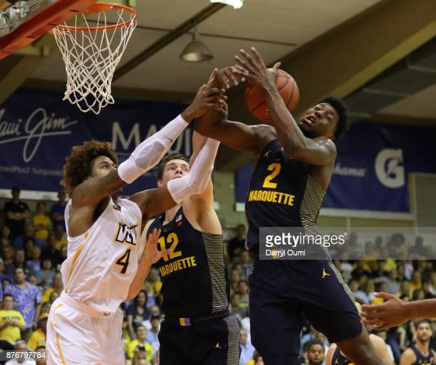 Sacar Anim and Matt Heldt of the Marquette Golden Eagles battle with Justin Tillman of the VCU Rams for a rebound during the first half of their game...