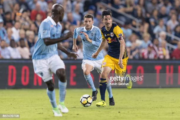 Sacha Kljestan of New York Red Bulls dribbles between two Sporting Kansas City players in the US Open Cup Final match at Children's Mercy Park on...