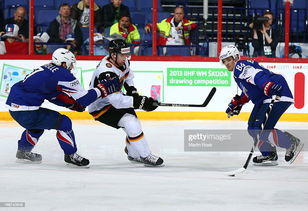 Sacha Treille (L) of France and Justin Krueger (C) of Germany battle for the puck during the IIHF World Championship group H match between France and Germany at Hartwall Areena on May 14, 2013 in Helsinki, Finland.