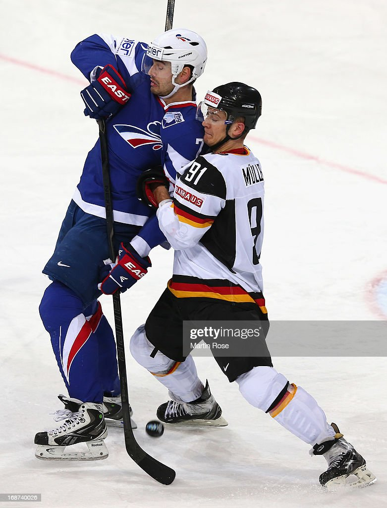 Sacha Treille (L) of France and <a gi-track='captionPersonalityLinkClicked' href=/galleries/search?phrase=Moritz+Mueller&family=editorial&specificpeople=853045 ng-click='$event.stopPropagation()'>Moritz Mueller</a> (R) of Germany battle for the puck during the IIHF World Championship group H match between France and Germany at Hartwall Areena on May 14, 2013 in Helsinki, Finland.
