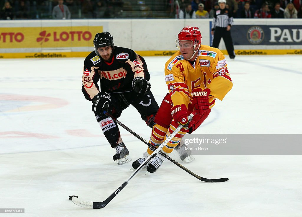 Sachar Blank (L) of Hannover and Travis Turnball (R) of Duesseldorf battle for the puck during the DEL match between Hannover Scorpions and Duesseldorfer EG at TUI Arena on November 23, 2012 in Hanover, Germany.