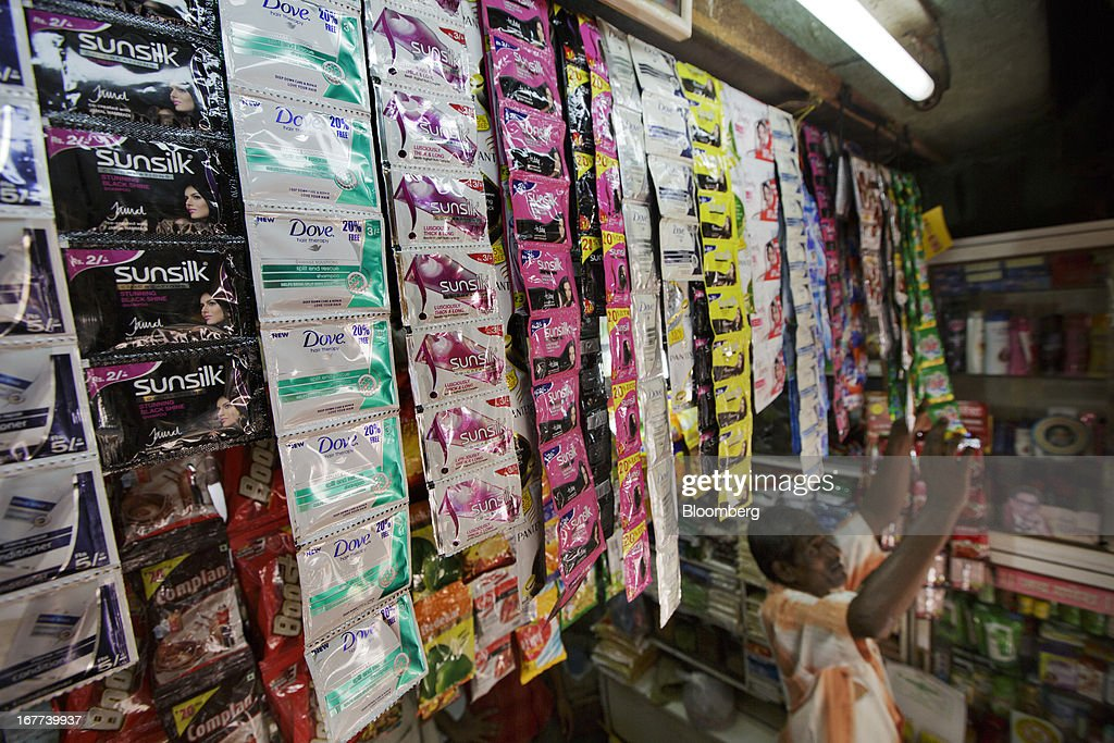 Sachets of Hindustan Unilever Ltd. Sunsilk shampoo, from left, and Dove shampoo are displayed for sale above a store attendant at a store in Mumbai, India, on Saturday, April 27, 2013. Consumer goods maker Hiindustan Unilever is scheduled to report earnings today. Photographer: Kuni Takahashi/Bloomberg via Getty Images