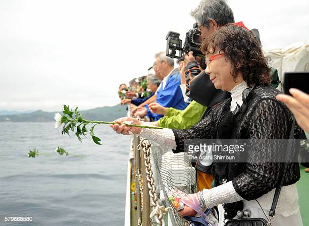 Sachiko Kumagai offers flowers to her husband who was killed in the 2011 tsunami while holding a letter written by their grandson during a memorial...