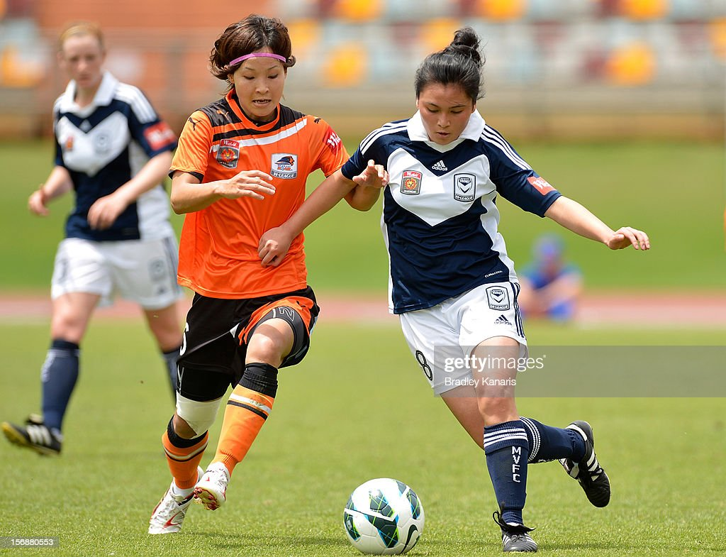 Sachiko Tatsuoka of the Roar and Cindy Lay of the Victory compete for the ball during the round six W-League match between the Brisbane Roar and the Melbourne Victory at the Queensland Sport and Athletics Centre on November 24, 2012 in Brisbane, Australia.