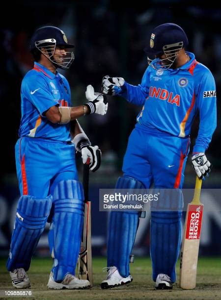 Sachin Tendulkar and Virender Sehwag of India bump fists during the 2011 ICC Cricket World Cup Group B match between India and the Netherlands at...