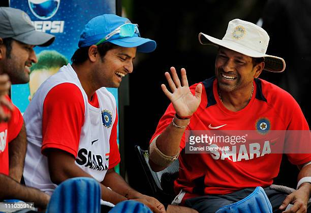 Sachin Tendulkar of India converses with team mates MS Dhoni and Suresh Raina during an Indian team training session at the PCA ground on March 29...