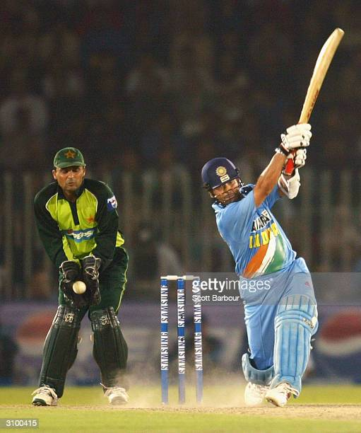 Sachin Tendulkar of India hits out during his innings of 141 as wicketkeeper Moin Khan of Pakistan watches during the second ODI between Pakistan and...