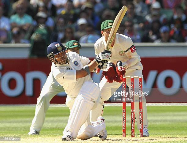 Sachin Tendulkar of India in action with Michael Clarke and Brad Haddin of Australia looking on during day two of the First Test match between...