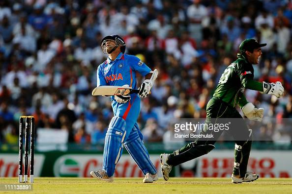 Sachin Tendulkar of India looks skywards as Kamran Akmal runs to congratulate Shahid Afridi of Pakistan who took the catch off the bowling of Saeed...